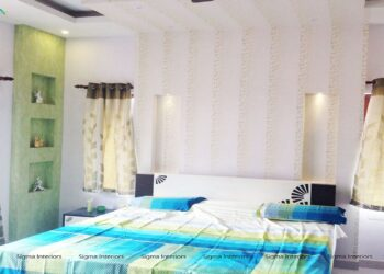 Gentle bedroom with view of bed with blue bedding flanked by tall greenish open ledges for decorative items