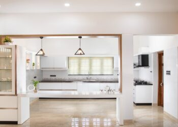 Image of a bright spacious kitchen in modern style with background modern tiles wall.